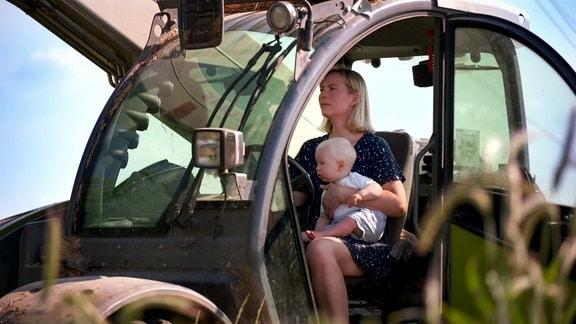 Frau mit Kleinkind bedient Maschinenfahrzeug