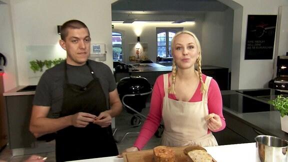 Eine junge Frau (Moderatorin) steht mit einem jungen Mann in einer Küche und lächelt mit vollem Mund den Betrachter an.