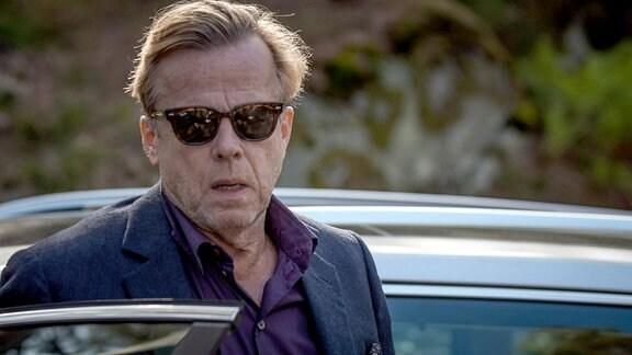 Wallander (Krister Henriksson) steht, mit Sonnenbrille, neben einem Auto.