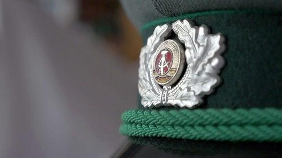 Emblem der DDR auf einer Mütze der Volkspolizei.