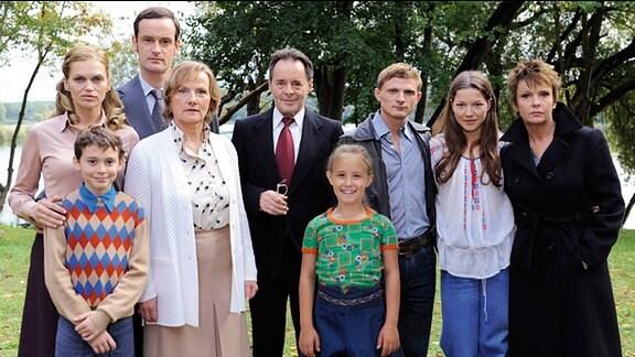 Die Familien Kupfer und Hausmann stehen im Park und posieren für ein Gruppenfoto.