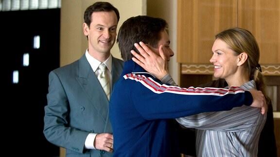 Falk (Jörg Hartmann, l.) und Vera Kupfer (Anna Loos, r.) umarmen ihren Sohn Roman (Ferdinand Lehmann, M.), nachdem dessen Nieren-Operation glücklich verlaufen ist.