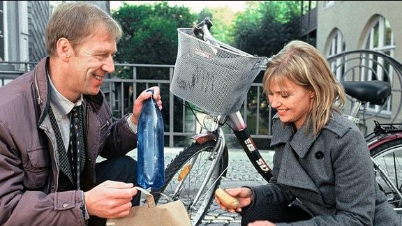 Pauske (Oliver Stritzel) hilft Karin (Katharina Böhm) dabei, herausgefallene Einkäufe wieder in die Einkaufstüten zu sammeln. Beide knien und lächeln sich an, Pauske fühlt sich sichtlich zu Karin hingezogen.