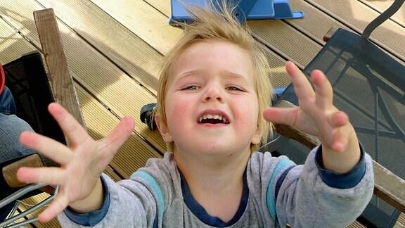 Kleiner Junge schaut mit erhobenen Händen quengelnd nach oben.