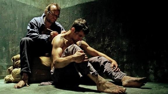 Ein älterer Mann schreibt seinem Gefängnismitinsassen auf den nackten Rücken
