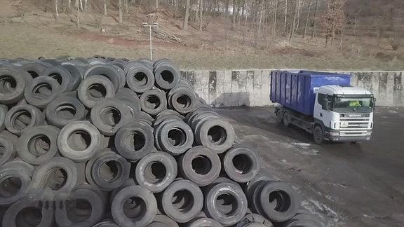 Auf einer Fläche liegt ein großer Stapel alter Reifen.