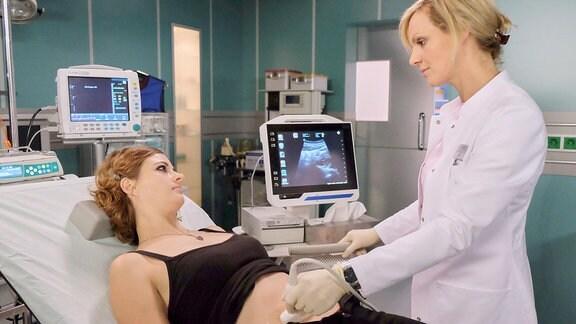 Die Ultraschallbilder zeigen Dr. Lea Peters (Anja Nejarri, re.), dass die Entzündung wahrscheinlich schon auf Lilith Schades (Linda Blümchen, li.) Eileiter übergegangen ist. Dr. Peters will minimalinvasiv operieren. Dann kann sie mehr sagen.