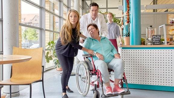 Dr. Philipp Brentano (Thomas Koch, hi.mi.) und seine Frau Arzu Ritter (Arzu Bazman, li.) waren gerade in der Cafeteria, als Irma Meltzer (Walfriede Schmitt, vo.re.) plötzlich in ihrem Rollstuhl zusammenbricht. Philipp ahnt, dass es sich sehr wahrscheinlich um einen Schlaganfall handelt.