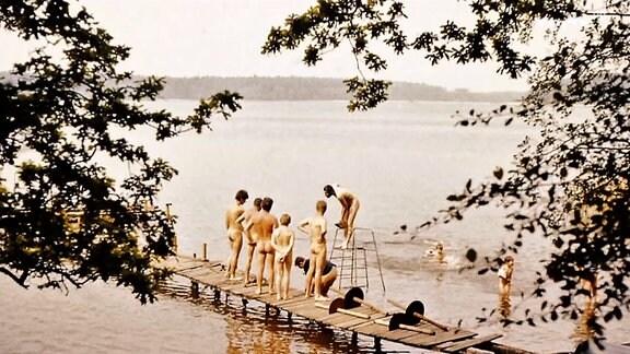 Nackte Badende auf einem Bootssteg.