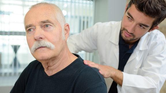 Therapeut behandelt Rücken eines Patienten