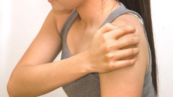 Eine Frau hält ihre schmerzende Schulter
