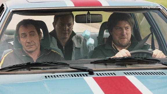 Drei Männer sitzen in einem Auto.