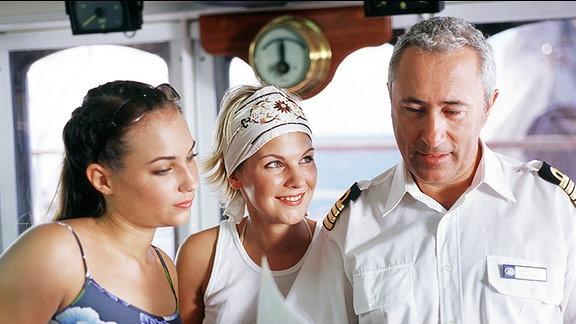 """Kapitän Arno Köhler (Robert Giggenbach) hat den beiden sympathischen Berliner Verkäuferinnen Lisa (Ivonne Schönherr, li.) und Grit (Julia Palmer-Stoll) aus Dankbarkeit dafür, dass sie seinem Sohn das Leben gerettet haben, einen Luxustrip auf der """"Royal Clipper"""" geschenkt."""