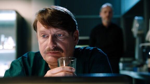 Ein Mann in OP-Kleidung hält ein Wasserglas, hinter ihm unscharf ein weiterer Mann