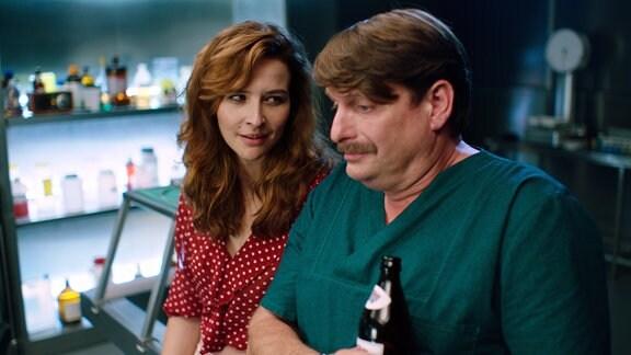 Eine Frau und ein Mann in OP-Kleidung unterhalten sich