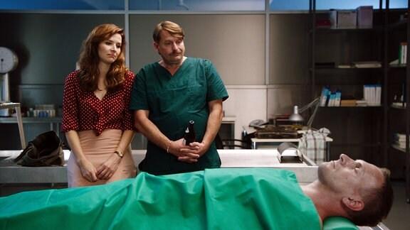 Eine Frau und ein Mann in OP-Kleidung in der Pathologie betrachten eine Leiche.