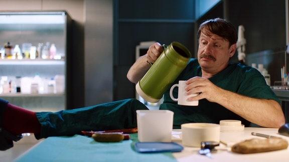 Mann in OP-Kleidung mit Bein auf dem Tisch frühstückt entspannt