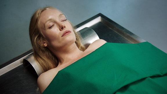 Schöne blonde Frau auf OP-Liege. Sie ist tot und mit grünem Tuch bis zum Hals abgedeckt