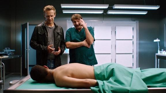 Zwei Männer unterhalten sich, daneben eine Leiche in der Pathologie