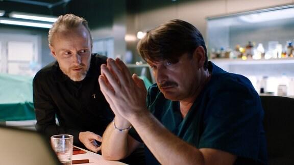 Zwei Männer unterhalten sich, einer hat die Hände gefaltet