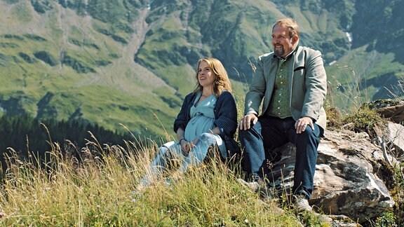 Svea sitzt mit ihrem Schwiegervater Joseph in gebirgiger Landschaft.