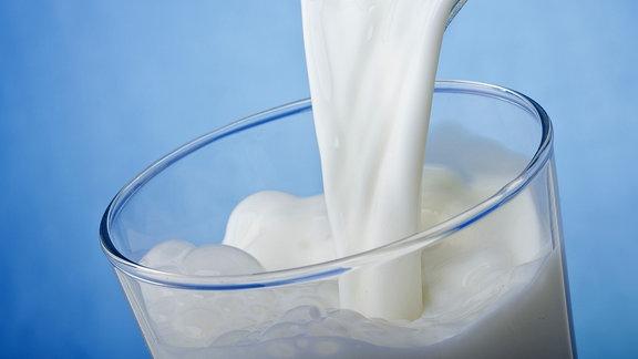 Milch wird in ein Glas geschüttet