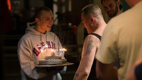 Junger Mann überreicht einen Geburtstagskuchen mit brennenden Kerzen