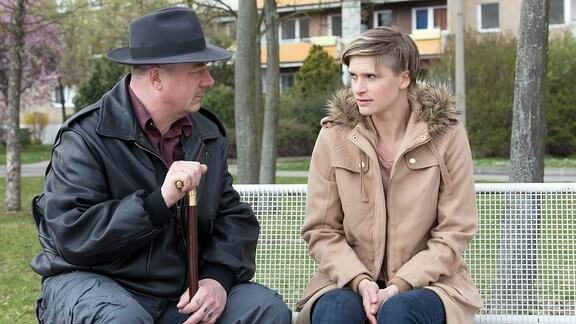 Älterer Mann mit Jüngerer Frau auf einer Parkbank