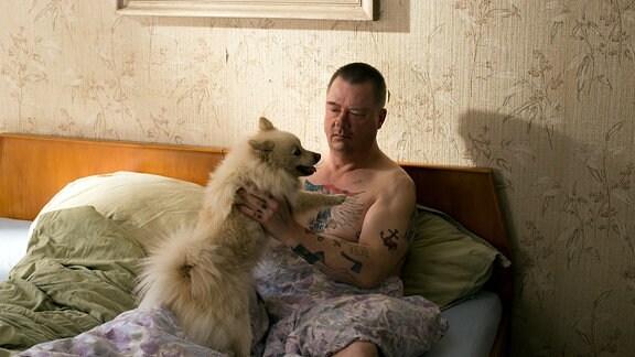 ein Mann sitz im Bett und spielt mit einem Hund