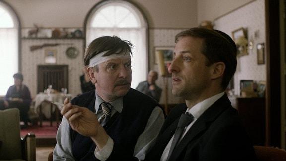 Zwei Männer im Gespräch. Einer trägt einen Kopfverband.