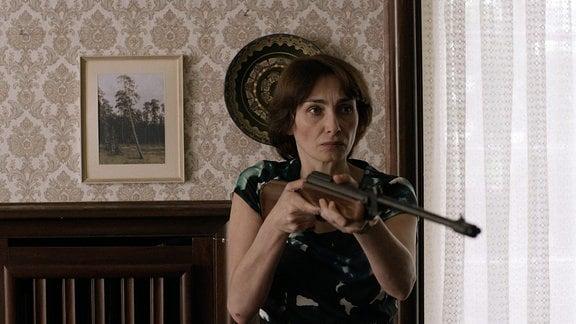 Frau hält ein Gewehr im Anschlag.
