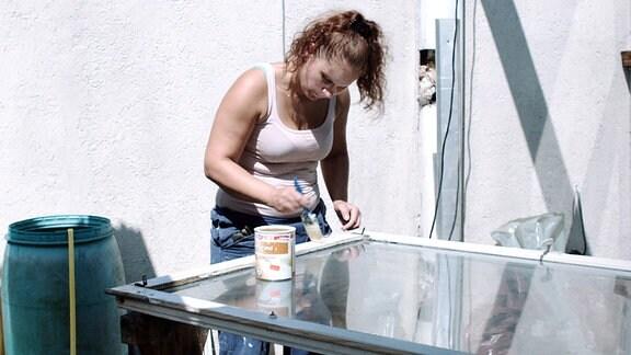 Janine Wolke als Jelena streicht alte Fenster.