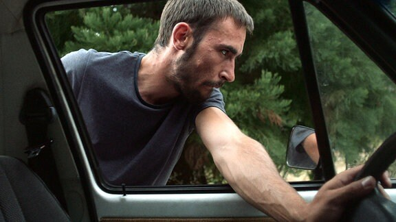 Junger Mann an einem Auto.
