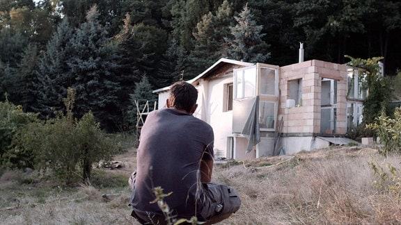 Ein junger Mann betrachtet ein unfertiges Haus aus der Ferne.