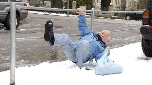 Älterer Mann rutscht auf verschneitem Gehweg aus