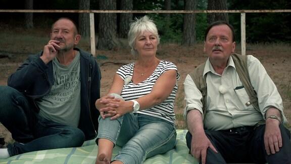 Zwei Männer und eine Frau auf einer Picknickdecke