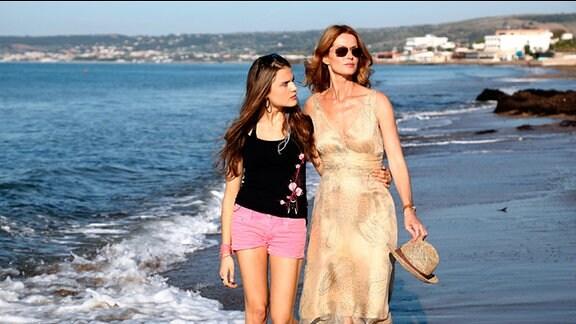 Susanne spaziert mit ihrer Tochter Caroline am Meer.