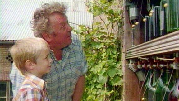 Opa und Enkel schauen im Garten auf eine Flaschenorgel.