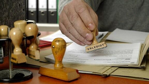 Ein Beamter setzt den Stempel ERLEDIGT unter eine Akte