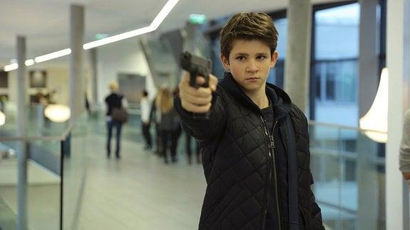 Felix (Enzo Gaier) mit Pistole in der Hand