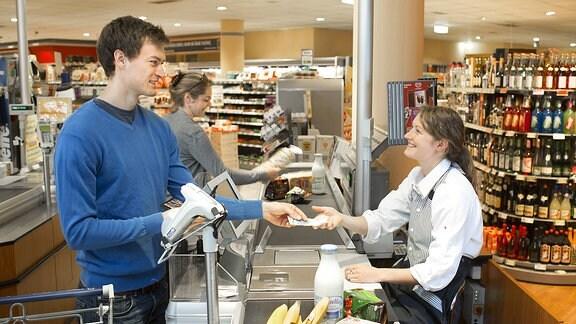 Ein Kunde bezahlt an einer Kasse im Supermarkt
