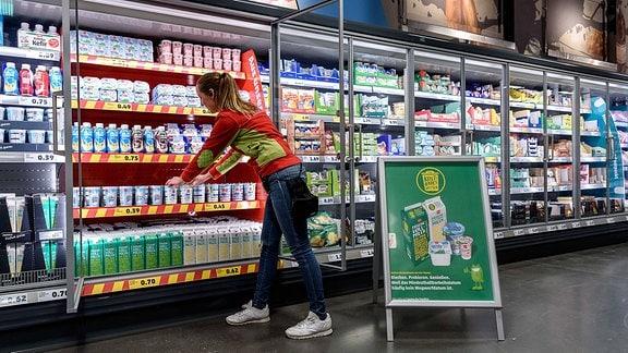 Eine Supermarktmitarbeiterin räumt ein Kühlregal ein