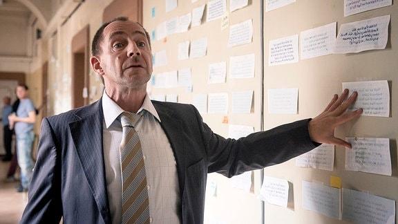 Kurt Stich (Thorsten Merten) vor der Wand an denen sie Roys Lottoscheine aufgehängt haben.