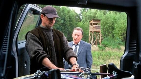 Karsten Dietz (Thomas Sarbacher, l.) nimmt Hauptkommissar Ehrlicher (Peter Sodann, r.) mit zum Luderplatz und verstaut zu diesem Zweck Ehrlichers Fahrrad in seinem Jeep.