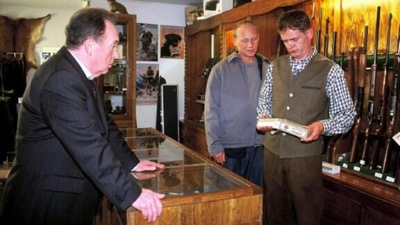 Ehrlicher (Peter Sodann, l.) und Kain (Bernd Michael Lade, m.) überprüfen Waffenhändler Georg Herboltz (Henning Peker, r.) in seinem Laden, ob er etwas mit dem Mord an Lothar Sofsky zu tun haben könnte.