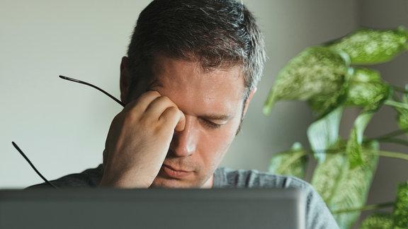 Ein müder Mann am Schreibtisch reibt sich seine trockenen Augen.