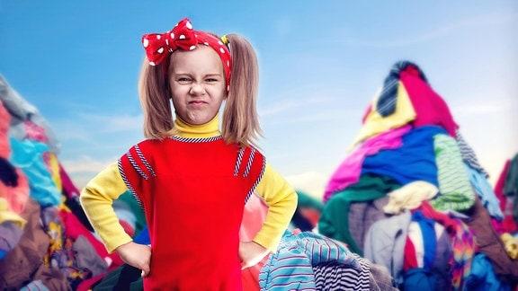 Kleines Mädchen mit ihren Händen auf den Hüften, steht umringt von Kleidungsstücken.