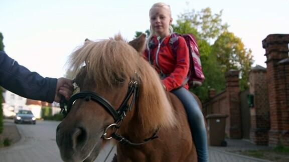 Ein Mädchen mit Schulranzen sitzt auf einem Pony.