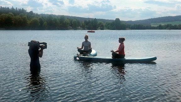 Entspannung und Abkühlung bringt die Yoga-Stunde auf dem SUP-Board mit Trainerin Michelle Butzert.