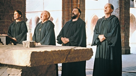 Benno (Michael Gwisdek, rechts), Tassilo (Matthias Brenner, 2. v. r.) und Arbo (Daniel Brühl, links) singen gemeinsam mit Abt Stephan (Traugott Buhre) im Kloster Auersperg das Morgengebet.